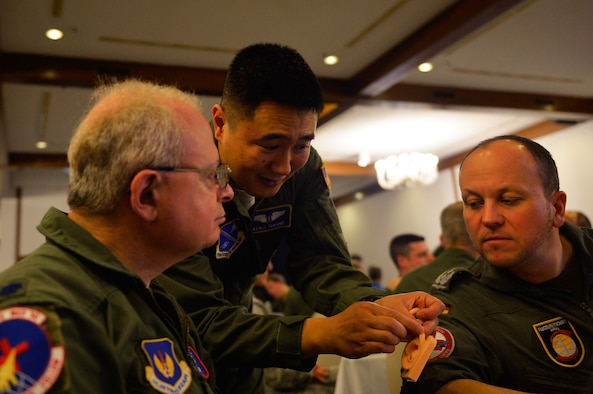 Lt. Col. Kenji Takado, a Pentagon flight medicine clinic flight surgeon, assists attendees during a battlefield acupuncture class on Ramstein Air Base, Germany, March 21, 2017. Battlefield acupuncture emerged in the early 2000s as a way to give quick pain relief treatment to troops in combat environments, and has since made its way into non-combat applications. (U.S. Air Force photo by Airman 1st Class Joshua Magbanua)