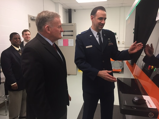 Major Ryan O'Hara (right), assistant professor, Graduate School of Engineering and Management, Air Force Institute of Technology, Wright-Patterson Air Force Base, demonstrates the capabilities of a new state-of-the-art 3D metal additive manufacturing system to Dr. Todd Stewart, AFIT director and chancellor, March 16.The system is a nearly $1 million investment that enables student researchers to digitally fabricate fully dense aerospace metal parts.(Skywrighter photo/Amy Rollins)