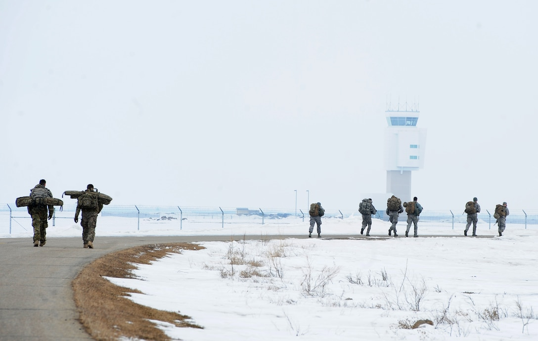 Airmen from the 5th Security Forces Squadron, ruck near the Air Traffic Control tower at Minot Air Force Base, N.D., March 16, 2017. The ruck was one of the many requirements for the Global Strike Challenge tryouts for the 5 SFS. (U.S. Air Force photo/Senior Airman Kristoffer Kaubisch)