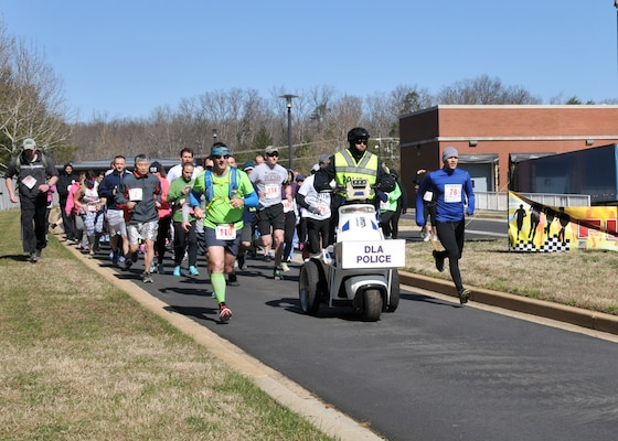 Runners and walkers depart the starting line on a brisk March day.