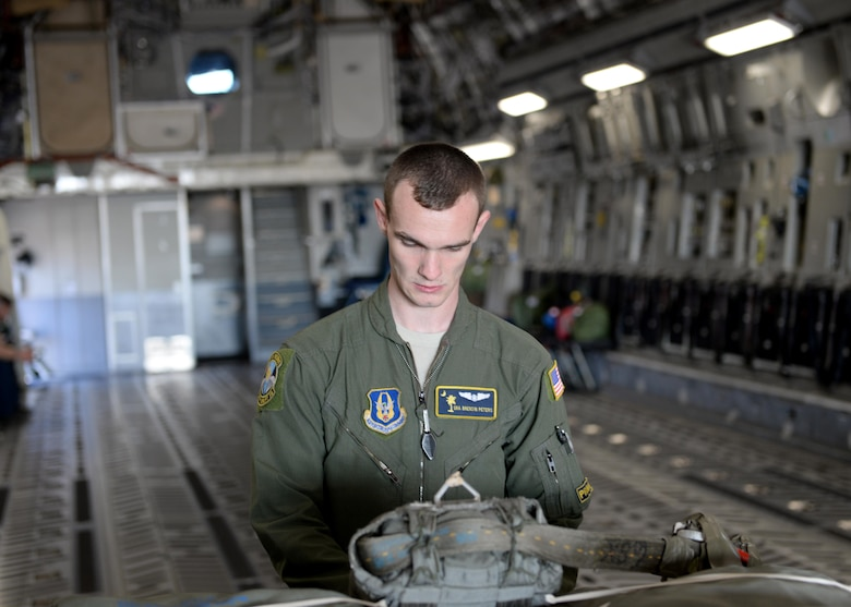 U.S. Air Force Senior Airman Brendin Peters, 317th Airlift Squadron loadmaster, secures a cargo training pallet on a U.S. Air Force C-17 Globemaster III cargo aircraft, March 17, 2017, Altus Air Force Base, Oklahoma. Brendin Peters participated in a refueling training mission where his crew's C-17 was refueled by a U.S. Air Force KC-135 Stratotanker refueling aircraft piloted by his father U.S. Air Force Col. Craig Peters, 940th Air Refueling Wing commander. (U.S. Air Force photo by Airman 1st Class Jackson N. Haddon/Released)