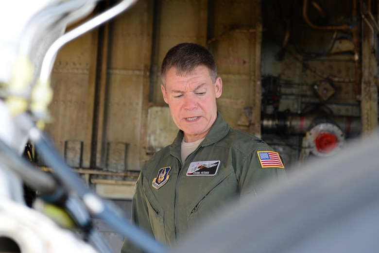U.S. Air Force Col. Craig Peters, 940th Air Refueling Wing commander, preforms a pre-flight safety check on a U.S. Air Force KC-135 Stratotanker refueling aircraft, March 17, 2017, at Altus Air Force Base, Oklahoma. Peters participated in a refueling training mission where his KC-135 refueled a U.S. Air Force C-17 cargo aircraft which his son, U.S. Air Force Senior Airman Brendin Peters, 317th Airlift Squadron loadmaster, was training aboard. (U.S. Air Force photo by Airman 1st Class Cody Dowell/Released)