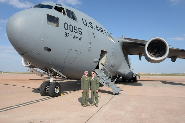 U.S. Air Force Senior Airman Brendin Peters (left), 317th Airlift Squadron loadmaster and U.S. Air Force Col. Craig Peters, 940th Air Refueling Wing commander, reunite in front of a U.S. Air Force C-17 Globemaster III cargo aircraft after a training mission, March 17, 2017, at Altus Air Force Base, Oklahoma. Brendin Peters participated in a refueling training mission where his crew's C-17 was refueled by a U.S. Air Force KC-135 Stratotanker refueling aircraft piloted by his father Craig Peters. (U.S. Air Force photo by Airman 1st Class Cody Dowell/Released)