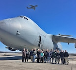 Regional airport managers from western Massachusetts and New England take a break for a photo in front of a C-5M Super Galaxy at Westover, March 23, 2017, while a C-5A Galaxy flies overhead. The managers toured the Dover Air Force Base, Del.-based C-5M and were briefed on the 439th Airlift Wing's eventual modernization to the M-models, beginning later into 2017. Westover Air Reserve Base is a joint-use airfield, with the Air Force sharing its runways with the adjacent Westover Metropolitan Airport. (U.S. Air Force photo/Master Sgt. Andrew Biscoe)