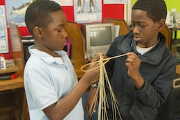 Students from Miracle Academy wove sweetgrass discs with sweetgrass from the Charleston District's Cooper River Rediversion Project, which were hung around a sweetgrass cross at Mother Emanuel AME Church.