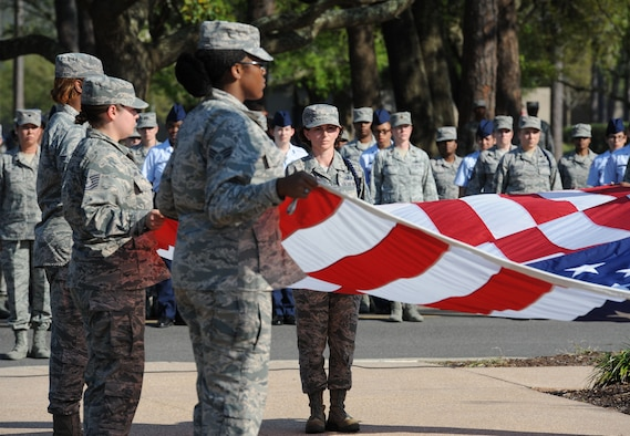 "Master Sgt. Amber Pacheco, 81st Training Group Air National Guard liaison, participates in a flag folding ceremony during a Women's History Month all-female retreat ceremony March 21, 2017, on Keesler Air Force Base, Miss. The theme of 2017 WHM is ""Honoring Trailblazing Women in Labor and Business"" to honor women who have successfully challenged the female role in business and the paid labor force (U.S. Air Force photo by Kemberly Groue)"