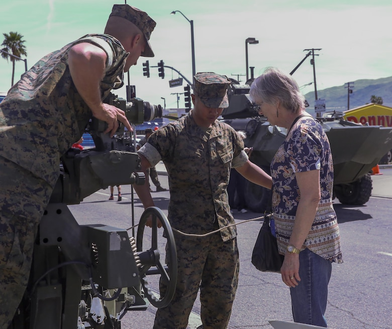 Marines with 3rd Battalion, 11th Marine Regiment, explain the mechanics of a Light Armored Vehicle to a Twentynine Palms resident during the 17th annual Car Show & Street Fair in Twentynine Palms, Calif., March 18, 2017. The Twentynine Palms Chamber of Commerce hosted the event to bring the community together. (U.S. Marine Corps photo by Lance Cpl. Natalia Cuevas)