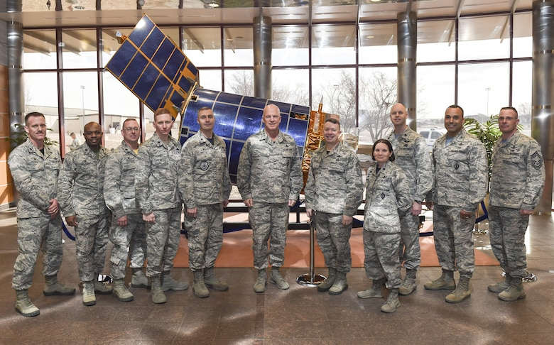 Gen. Jay Raymond, commander of Air Force Space Command, center, and Chief Master Sgt. Brendan Criswell, AFSPC command chief, poses with Team Buckley leadership cadre in front of a Defense Support Program half-scale satellite March 17, 2017, at Buckley Air Force Base, Colo. Buckley boasts America's Premier Space Wing, installation support to 95 multiservice and multinational units, a population of over 94,000 Team Buckley members, and a mission that is critical to the nation's safety. (U.S. Air Force photo by Tech. Sgt. Nicholas Rau)