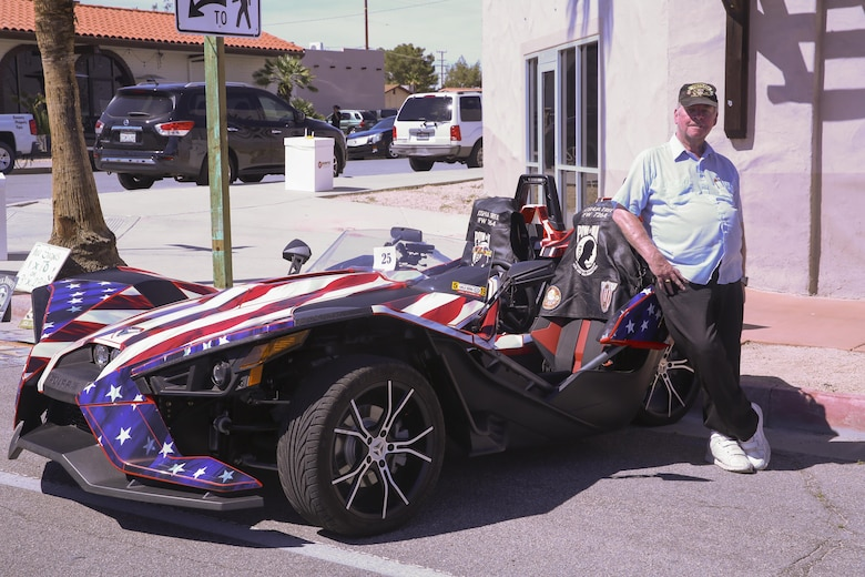 Retired Army Vietnam veteran Mike Hammer shows off his Puller Slingshot car painted as the American flag car during the 17th annual Car Show & Street Fair in Twentynine Palms, Calif., March 18, 2017. The Twentynine Palms Chamber of Commerce hosted the event to bring the community together. (U.S. Marine Corps photo by Lance Cpl. Natalia Cuevas)