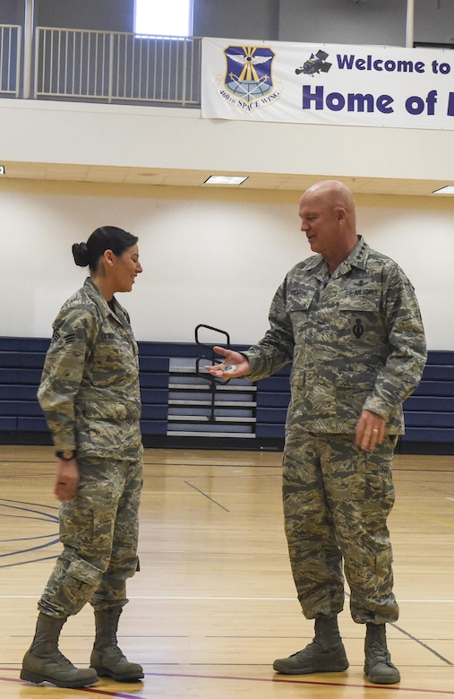 Senior Airman Sarah Gilbert, 460th Medical Group public health, left, receives a coin from Gen. Jay Raymond, commander of Air Force Space Command, for excellence March 17, 2017, at Buckley Air Force Base, Colo. Buckley boasts America's Premier Space Wing, installation support to 95 multiservice and multinational units, a population of over 94,000 Team Buckley members, and a mission that is critical to the nation's safety. (U.S. Air Force photo by Tech. Sgt. Nicholas Rau)