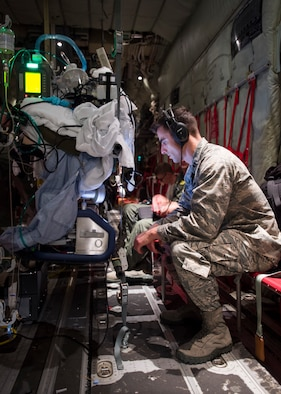 Capt. Jeffrey Dellavolpe, 959th Medical Operations Squadron critical care physician, regulates the Extracorporeal Membrane Oxygenation system during a flight to San Antonio Military Medical Center, Joint Base San Antonio-Fort Sam Houston, Texas. ECMO is a heart-lung bypass system that circulates blood through an external artificial lung and sends it back into the patient's bloodstream. (U.S. Air Force photo/Staff Sgt. Kevin Iinuma)