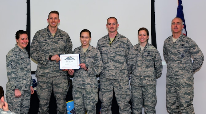 U.S. Air Force 2nd Lt. Seth Gammon, second from left, an intel analyst assigned to the 509th Operations Support Squadron, receives a Whiteman Company Grade Officer Council (CGOC) Bars and Stars award from members of the CGOC and Col. Mark Ely, far right, the 509th Bomb Wing vice commander, at Whiteman Air Force Base, Mo., March 13, 2017. Gammon implemented an internal briefing program within the intelligence flight to inform Airmen of enemy threats and to improve the briefing skills of the intelligence personnel. He also manages the fitness program for his squadron where he facilitated the execution of 27 quarterly mock assessment tests to improve passing scores and rates. (U.S. Air Force photo by Airman 1st Class Jazmin Smith)