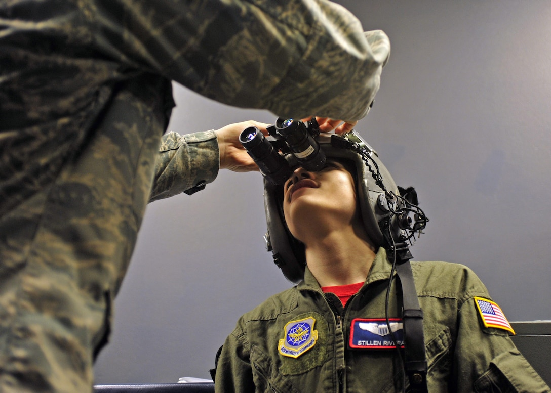"""Stillen Rivera, Team McChord's newest """"Pilot for a Day"""" participant, gets fitted for night-vision goggles at the 62nd Operations Support Squadron Aircrew Flight Equipment section, March 23, 2017 at Joint Base Lewis-McChord, Wash. Stillen was also able to test out the SERE emergency evacuation hanging harness, climb to the top of the control tower, visit the base fire station, fly a C-17 simulation and board a C-17 static on the McChord Field flightline. (U.S. Air Force photo/Staff Sgt. Whitney Amstutz)"""