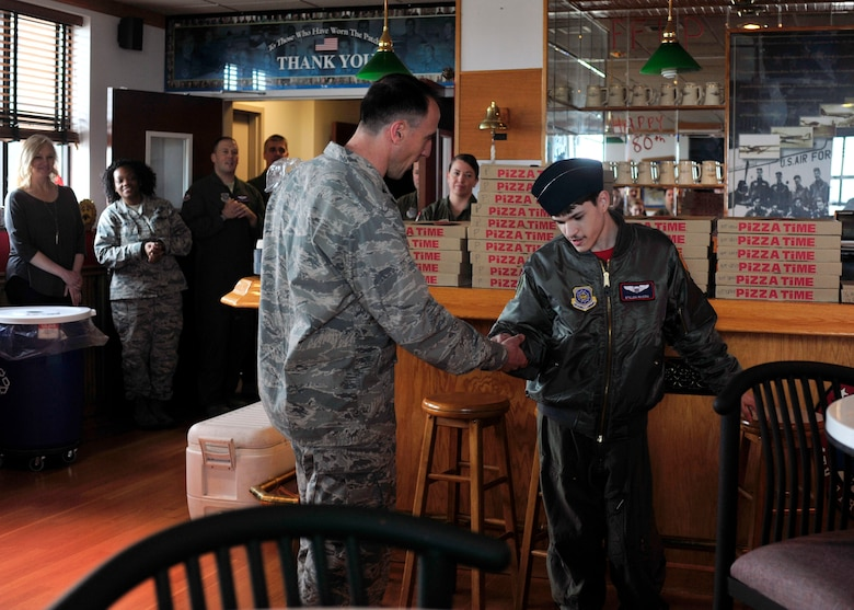 """Col. Leonard Kosinski (left), 62nd Airlift Wing commander, coins Stillen Rivera, Team McChord's newest """"Pilot for a Day"""" participant, during a pizza party at the 4th Airlift Squadron, March 23, 2017 at Joint Base Lewis-McChord, Wash. The """"Pilot for a Day"""" program, which has been hosted by Team McChord for several years, provides youth with a limiting disability the opportunity to live out their life-long dreams of aviation and share those memorable experiences with their family by their side. (U.S. Air Force photo/Staff Sgt. Whitney Amstutz)"""