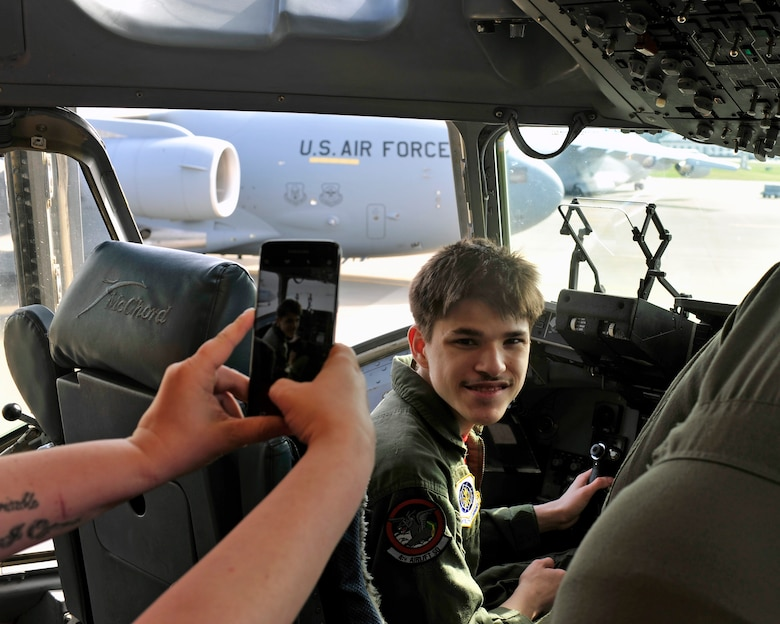 """Stillen Rivera, Team McChord's newest """"Pilot for a Day"""" participant, smiles on the flight deck of a C-17 during his daylong visit to McChord Field, March 23, 2017 on the McChord flightline. The """"Pilot for a Day"""" program has been hosted by Team McChord for the past several years and seeks to fulfil the dreams of youth with limiting disabilities. (U.S. Air Force photo/Staff Sgt. Whitney Amstutz)"""