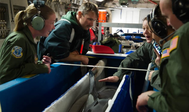 Members from the 446th Aeromedical Evacuation Squadron examine a dolphin from the U.S. Navy's Marine Mammal Program flying aboard a C-17 Globemaster III operated March 13, 2017. The 446th AES were providing assistance, as required, by the dolphin's handler. (U.S. Air Force photo by David L. Yost)