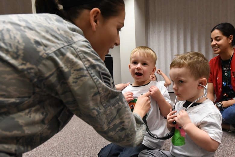 Senior Airman Elenacorozal  Denny, 4th Medical Operations Squadron medical technician, teaches children from the 4th Force Support Squadron Child Development Center how to use a stethoscope, March 21, 2017, at Seymour Johnson Air Force Base, North Carolina. The children listened to each other's heartbeats, read books about the body and toured the pediatric clinic. (U.S. Air Force photo by Airman 1st Class Victoria Boyton)