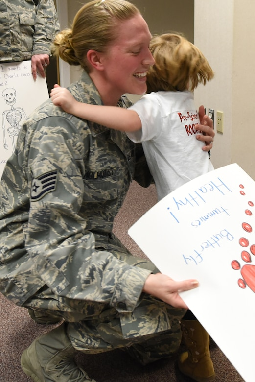 Staff Sgt. Erin Holmquist, 4th Medical Operations Squadron medical laboratory technician, hugs a preschooler from the 4th Force Support Squadron Child Development Center, March 21, 2017, at Seymour Johnson Air Force Base, North Carolina. The children presented the laboratory staff with a thank you card during a field trip visit. (U.S. Air Force photo by Airman 1st Class Victoria Boyton)