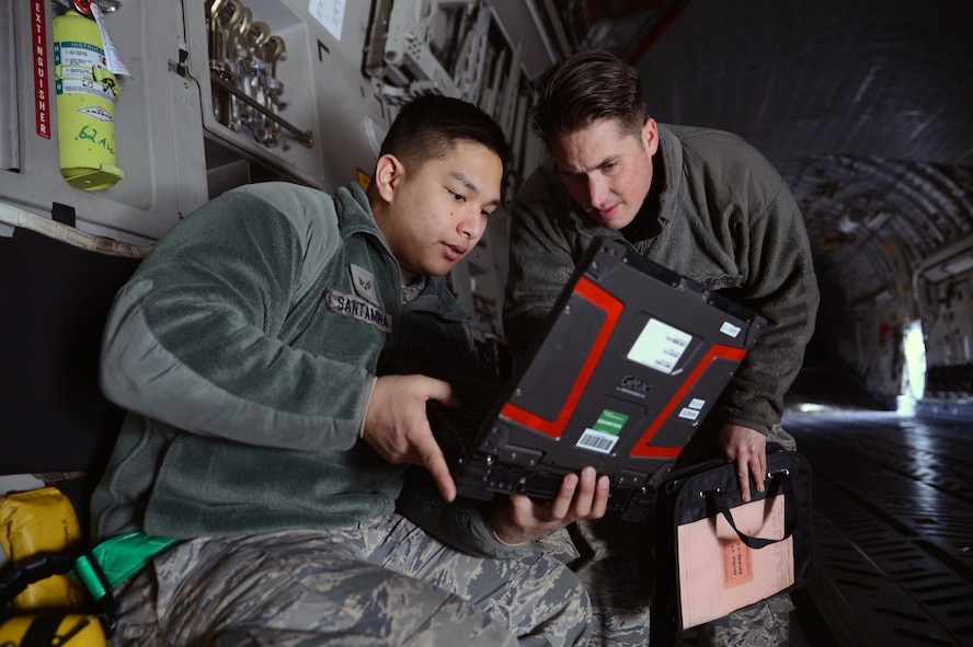 Senior Airman Facundo Santamina (left), 62nd Aircraft Maintenance Squadron crew chief and Staff Sgt. James Pomeroy, 62nd AMXS crew chief, review a technical order prior to performing maintenance on a C-17 Globemaster III aircraft March 20, 2017 at Joint Base Lewis-McChord, Wash. In order to inspect and diagnose aircraft maintenance issues, crew chiefs go through more than five months of technical training and months of on the job training. (U.S. Air Force photo/Senior Airman Jacob Jimenez)