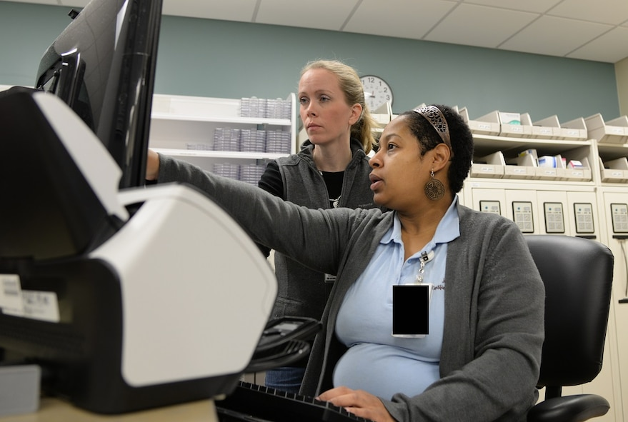 Juliette Zuber, 14th Medical Support Squadron Pharmacy, and Katie Steinback, a student in the Education Center's pharmacy technician program, discuss day-to-day pharmacy operations March 13, 2017, at Columbus Air Force Base, Mississippi. The new equipment makes learning how to be a pharmacy technician easier due to the user-friendly applications. (U.S. Air Force photo illustration by Airman 1st Class Beaux Hebert)
