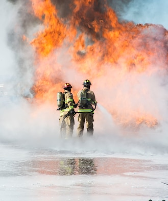 Two airmen from the Mountain Home Air Force Base Fire Department practice extinguishment techniques during a live-fire exercise here, Feb. 16, 2017. Airmen at the Fire Protection Flight train for the worst during their training scenarios. (U.S. Air Force photo by Senior Airman Malissa Lott/Released)
