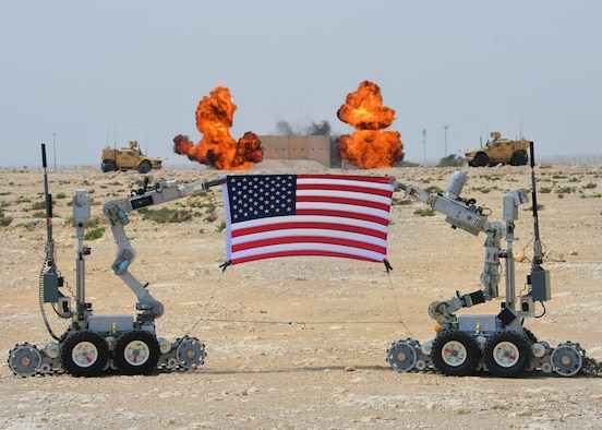 """Two """"fireball"""" charges go off behind a U.S. flag being held by F6A bomb disposal robots at Al Udeid Air Base, Qatar, March 17, 2017. The 379th Expeditionary Civil Engineer Squadron Explosive Ordnance Flight set off several rounds of explosives to mark the grand opening of their new EOD range at Al Udeid. (U.S. Air Force photo by Senior Airman Miles Wilson)"""