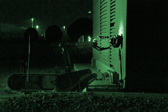 """A PACBOT bomb disposal robot removes an improvised explosive device from a transformer during exercise """"Vigilant Walrus"""" at Al Udeid Air Base, Qatar, March 21, 2017. During the exercise, Airmen with the 379th Expeditionary Civil Engineer Squadron Explosive Ordnance Disposal Flight were forced to work at night without the use of white light. (U.S. Air Force photo illustration by Senior Airman Miles Wilson)"""