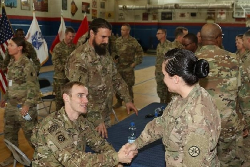 Retired Army Sgt. Willard Hoyum, wheeled vehicle mechanic, formerly with A company, 307th Brigade Support Battalion, 82nd Airborne Division, shakes the hand of a deployed Soldier, March 14, 2017, Camp Arifjan, Kuwait. The meet and greet concluded the first town hall meeting Soldiers of Operation Proper Exit will give prior to returning to the location where they received their combat injuries.