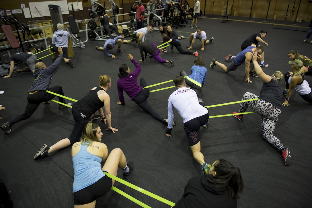 Participants perform warm up stretches during the LifeFit Tour exercise demonstration March 21, 2017, at Yokota Air Base, Japan. The goal of the event was to bring like-minded military members and their families together in a fun learning experience on fundamental exercise safety and form. (U.S. Air Force photo by Airman 1st Class Donald Hudson)
