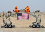 "Two ""fireball"" charges go off behind a U.S. flag being held by F6A bomb disposal robots at Al Udeid Air Base, Qatar, March 17, 2017. The 379th Expeditionary Civil Engineer Squadron Explosive Ordnance Flight set off several rounds of explosives to mark the grand opening of their new EOD range at Al Udeid. (U.S. Air Force photo by Senior Airman Miles Wilson)"
