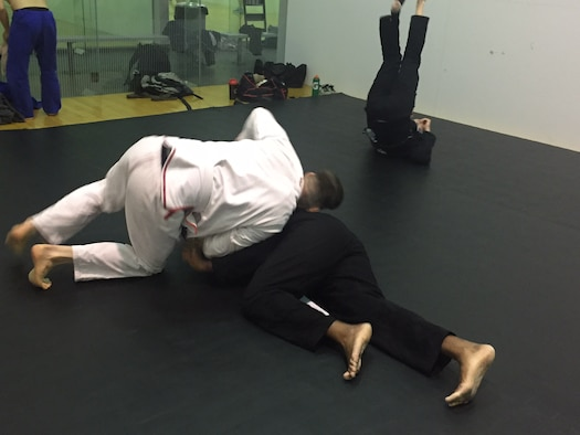 Tech. Sgt. Christopher Elliott, antiterrorism officer, 178th Security Forces Squadron, Springfield Air National Guard Base (left), grapples with Lt. Col.James Finlayson, National Air and Space Intelligence Center, during a Brazilian jiu jitsu class March 17 at Wright Field Fitness Center.