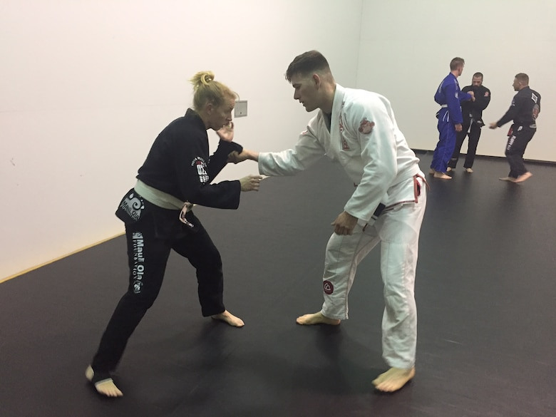 Chelsea Rorer (left), an emergency nurse at Miami Valley Hospital and whose wife is a physician at the Wright-Patterson Medical Center, practices breaking the grip ofTech. Sgt. Christopher Elliott, anti-terrorism officer, 178th Security Forces Squadron, Springfield Air National Guard Base, during the Brazilian jiu jitsu class March 17. (Skywrighter photo/Amy Rollins)