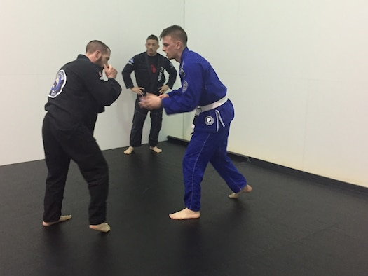 Adam Brown (left), combustion research engineer, Propulsion Directorate,Air Force Research Laboratory, gets ready to grapple with Airman 1st Class Brenden Rogers, National Air and Space Intelligence Center, during a Brazilian jiu jitsu class March 17 at Wright Field Fitness Centerwhile coach David Reeves observes. (Skywrighter photo/Amy Rollins)