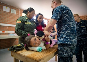 MAYAPO, Colombia (March 25, 2017) - Hospital Corpsman 2nd Class Joshua Crisano, a native of Williamsburg, Va., assigned to Naval Hospital Jacksonville, Fla., teaches physical therapy stretches to the mother of a host nation child at the Continuing Promise 2017 (CP-17) medical site in Mayapo, Colombia. CP-17 is a U.S. Southern Command-sponsored and U.S. Naval Forces Southern Command/U.S. 4th Fleet-conducted deployment to conduct civil-military operations including humanitarian assistance, training engagements, and medical, dental, and veterinary support in an effort to show U.S. support and commitment to Central and South America. (U.S. Navy photo by Mass Communication Specialist 2nd Class Shamira Purifoy)