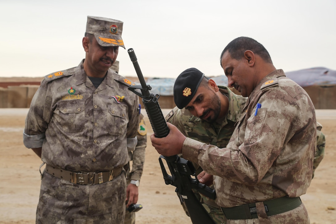 A Danish soldier deployed in support of Combined Joint Task Force – Operation Inherent Resolve, and Iraqi security forces officers verify serial numbers on a M16A2 rifle during Iraq Train and Equip Funding - equipment issue at Al Asad Air Base, Iraq, March 18, 2017. The Iraq Train and Equip Funding Program, is facilitated by CJTF – OIR, provides essential weapons and equipment to vetted partner forces as part of the building partner capacity mission. CJTF – OIR is the global Coalition to defeat ISIS in Iraq and Syria. (U.S. Army photo by Sgt. Lisa Soy)