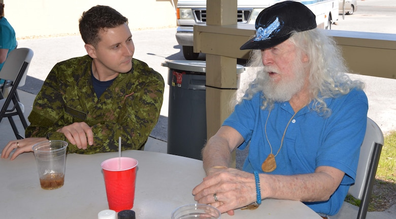 Royal Canadian Air Force Sgt Evan Ryan, Continental U.S. NORAD Region-1st Air Force (Air Forces Northern) Communication & Information Directorate, talks with Dennis Belk, a resident of the Clifford Chester Sims State Veterans Nursing Home, during a luncheon at American Legion Post 392 in Panama City. Event organizer David Shaw, a Legion member from CONR-1st AF (AFNORTH), said the luncheon was an opportunity to spend time with the veterans and recognize them for their selfless service and sacrifice. (Photo by Mary McHale)