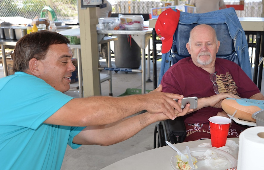 Dan Phillips, Continental U.S. NORAD Region-1st Air Force (Air Forces Northern) Communication & Information Directorate, shows a photo from his phone to Johnny Mack Jones, a resident of the Clifford Chester Sims State Veterans Nursing Home, during a luncheon at American Legion Post 392 in Panama City. Event organizer David Shaw, a Legion member from CONR-1st AF (AFNORTH), said the luncheon was an opportunity to spend time with the veterans and recognize them for their selfless service and sacrifice. (Photo by Mary McHale)