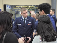 First Lt. Eric Kenney, 390th Cyberspace Operations Center, speaks with high schoolers about the Air Force cyber mission during an information fair at the annual Mayor's Cyber Cup banquet March 25 in San Antonio, Texas. The students all competed in the Air Force Association CyberPatriot challenge, a nationwide program in which teams of students learn to harden network security and then compete to defend systems against intrusions.