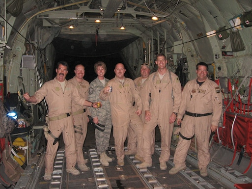 Chief Master Sgt. Milissa Fowler, (third from the left) 153rd Airlift Wing, Force Support Squadron superintendent, poses in the back of a C-130H during her support of Operation Enduring Freedom in 2009 where she assisted with protocol. (Courtesy photo)