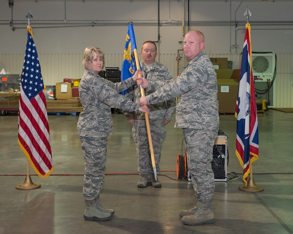 153rd Mission Support Group Commander Col. Shelley Campbell passes the 153rd Command and Control Squadron guidon to incoming commander Lt. Col. Christopher Howard at an Assumption of Command ceremony, Sept. 29, 2015 at F.E. Warren AFB in Cheyenne, Wyoming. Howard has previously held a position as the commander of the 243rd Air Traffic Control Squadron. (U.S. Air National Guard photo by Master Sgt. Charles Delano/released)