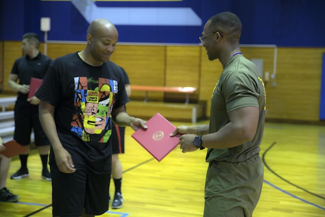 U.S Marine Corps Staff Sgt. Charles London, Marine Corps Air Station Iwakuni, Japan's first official Force Fitness Instructor, gives U.S. Marine Corps Cpl. Wesley Thompson, a supply administration specialist with Marine Air Group (MAG) 12, a certificate for completing an eight-week physical training course, March 17, 2017. Wesley was part of the first group of Marines to go through the course at MCAS Iwakuni. The recently implemented Force Fitness Instructors are capable of designing individual and unit-level holistic fitness programs, and they serve as subject matter experts on physical fitness and sports-related injury prevention.