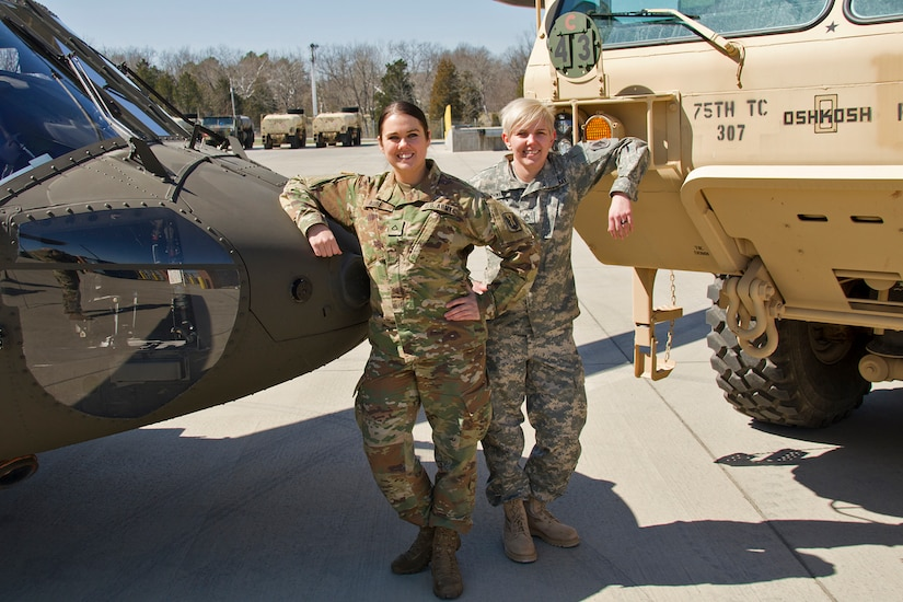 Pfc. Meghan Aube, left, and Staff Sgt. Kathleen Braithwaite stand with the military equipment they maintain on a daily basis. They are two of the few female mechanics in the Kentucky National Guard.