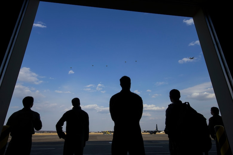 U.S. Air Force aircrews with the 36th Airlift Squadron watch U.S. Marine jumpers descend from an Air Force C-130H Hercules at Yokota Air Base, Japan, March 23, 2017, during jump week. The training not only allowed the Marines to practice jumping, but it also allowed the Yokota aircrews to practice flight tactics and timed-package drops. (U.S. Air Force photo by Yasuo Osakabe)