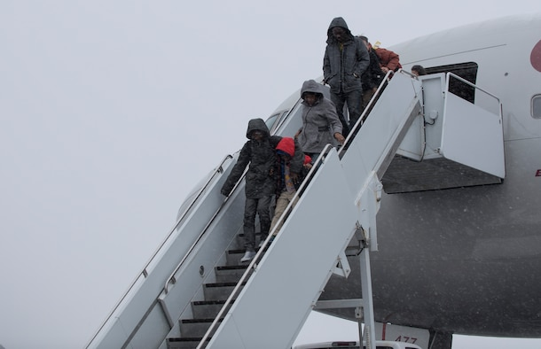 U.S. Air Force Airmen and families exit from the rotator at Misawa Air Base, Japan, Jan. 23, 2017. The terminal processes approximately 2,500 people for Space-Available. Space-A is the utilization of any vacant aircraft seating to charter military members to various AMC terminals for a low-cost fee. (U.S. Air Force photo by Airman 1st Class Sadie Colbert)