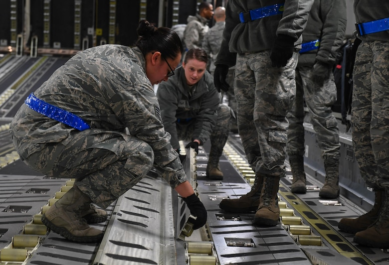 Staff Sgt. Jacquelyn Alvarez, 721st Aerial Port Squadron NCO in charge of the Unit Learning Center, helps a student flip rollers over inside a C-17 Globemaster III before loading cargo onto the aircraft on Ramstein Air Base, Germany, March 21, 2017. The Unit Learning Center provides new Airmen the training required for them to complete their upgrade training for passenger services, air freight, and ramp services. (U.S. Air Force photo by Senior Airman Tryphena Mayhugh)