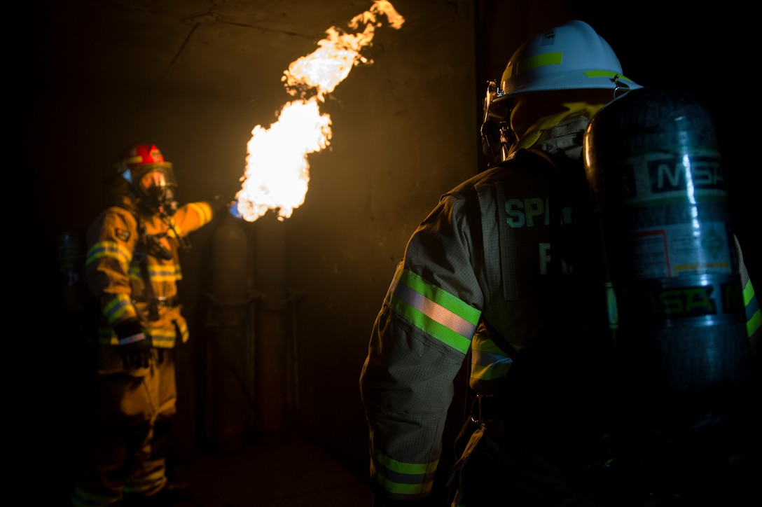 U.S. Air Force Staff Sgt. Jordan Schraner, 52nd Civil Engineer Squadron firefighter, shows Col. Steven Zubowicz, 52nd Mission Support Group commander, a controlled fire during a live fire exercise at Spangdahlem Air Base, Germany, March 23, 2017. The exercise provided firefighters with training such as hose advancement and practice extinguishing various types of fires. (U.S. Air Force photo by Airman 1st Class Preston Cherry)