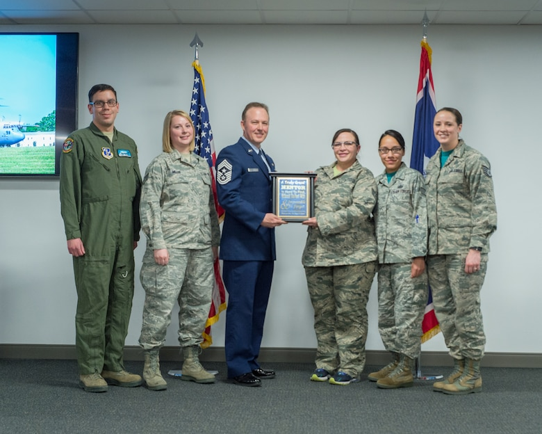 U.S. Air Force Staff Sgt. Rebekah Miller (second from the left) stands with other members of the Rising 6 Council as they make a presentation to retiring Chief Master Sgt. Michael Abbott, Mar. 10, 2017 in Cheyenne, Wyoming. Miller has been with the Wyoming Air National Guard for six years and is serving as a command post specialist. She has also been an officer with the Torrington police department for two years. (U.S. Air National Guard photo by Senior Master Sgt. Charles Delano/released)