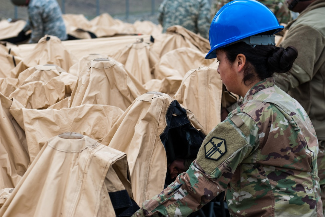 A soldier disassembles a deployable rapid assembly shelter (DRASH) at Joint Base Lewis-McChord, Washington, March 12, 2017. Soldiers from the 301st Maneuver Enhancement Brigade went through a series of maneuver and mobility exercises to ensure deployment readiness and demonstrate the brigade's ability to command and control in a tactical environment. (U.S. Army Reserve photo by Spc. Sean F. Harding/Released).