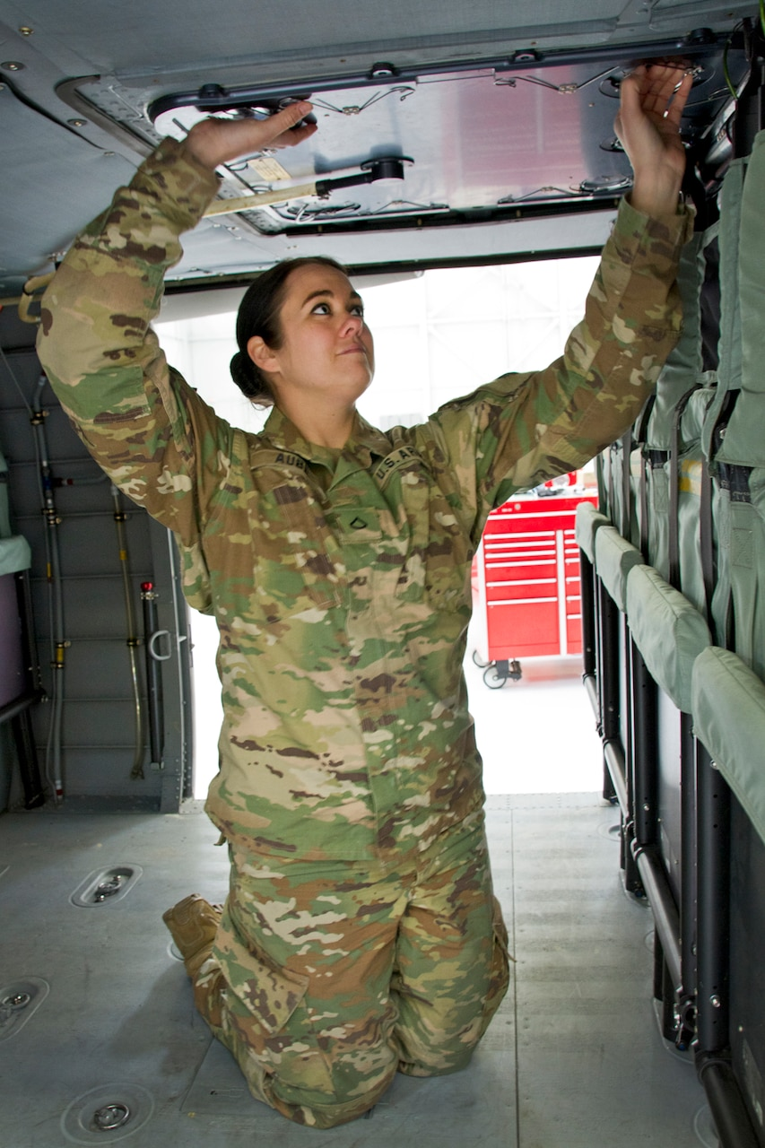 Army Pfc. Meghan Aube checks an emergency hatch on an UH-60 Blackhawk helicopter at the Army Aviation Support Facility in Frankfort, Ky., March 16, 2017. Kentucky Army National Guard photo by Staff Sgt. Scott Raymond