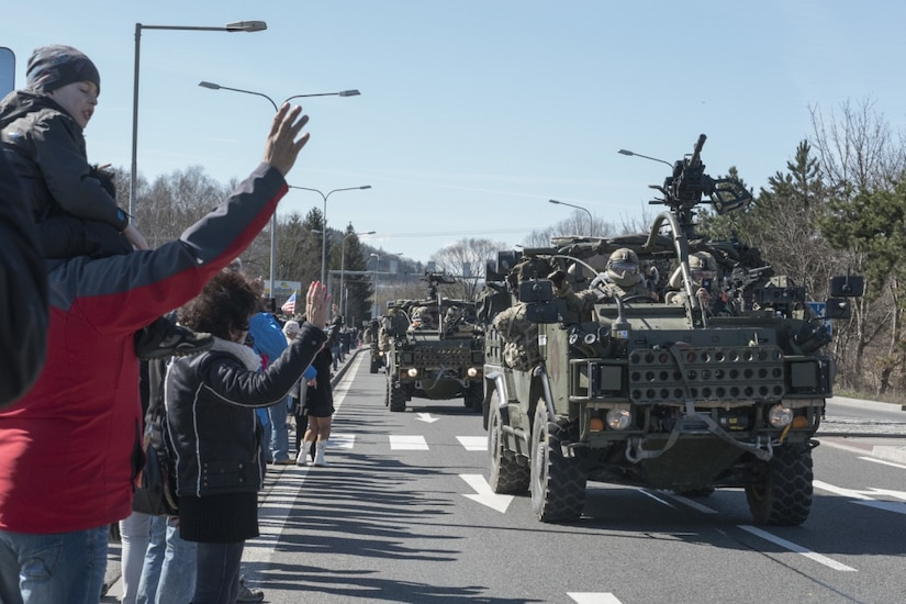 Polish citizens greet the soldiers of Battle Group Poland as the convoy of tactical vehicles crosses the border from the Czech Republic into Poland March 26, 2017. The contingency force of U.S., U.K. and Romanian soldiers convoyed to Orzysz, Poland, where they will integrate with the Polish 15th Mechanized Brigade, 16th Infantry Division. Army photo by Sgt. 1st Class Patricia Deal